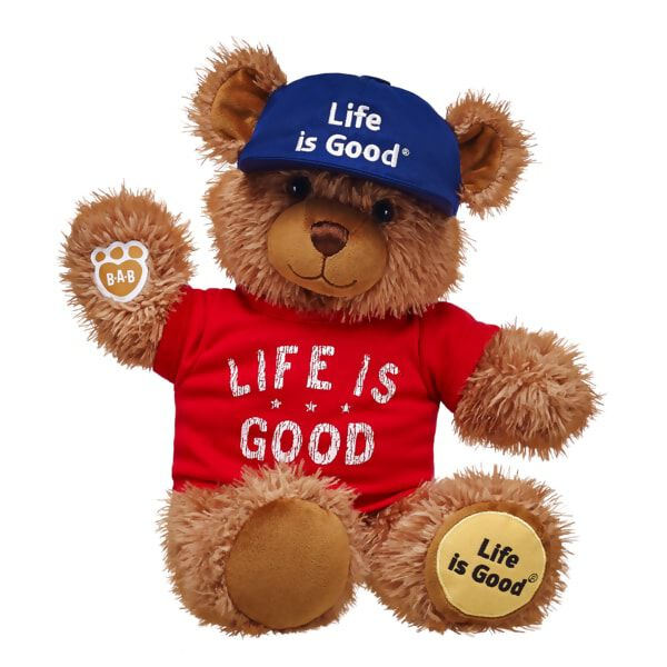"This Life is Good Bear is ready for whatever adventure the day has in store! Featuring the Life is Good Yellow Dot logo on its paw pad, this super soft light brown bear is outfitted with the coolest Life is Good clothing. The bright red tee and sporty blue ball cap both feature the optimistic Life is Good logo in white lettering. &#169 2016 The Life is Good Company. All Rights Reserved. ""Life is Good"" is a registered trademark and the Yellow Dot Logo a trademark of the Life is Good Company."